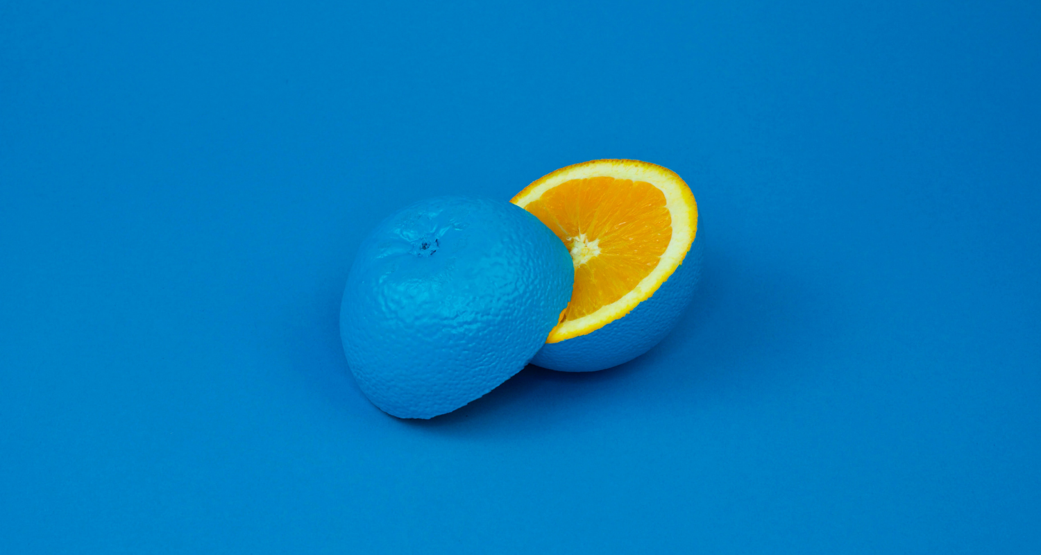 An orange sliced in two, coloured blue